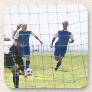mature men kicking soccer ball towards drink coaster