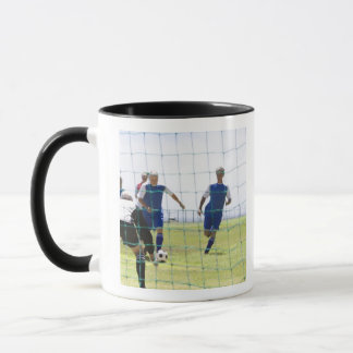 mature men kicking soccer ball towards mug