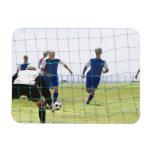 mature men kicking soccer ball towards rectangular magnet