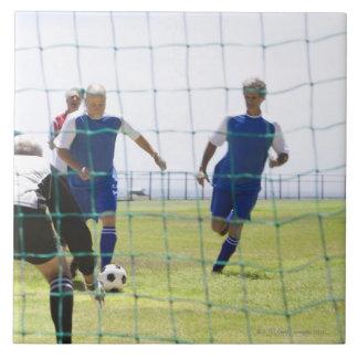 mature men kicking soccer ball towards tile