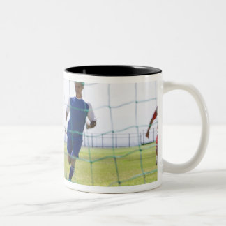 mature men kicking soccer ball towards Two-Tone coffee mug