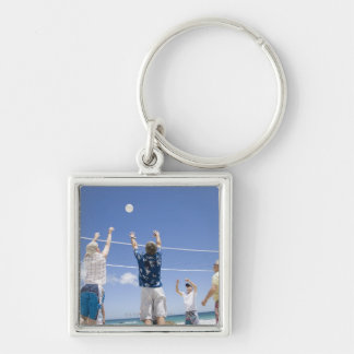 Mature men leaping for volley ball on beach, Silver-Colored square keychain