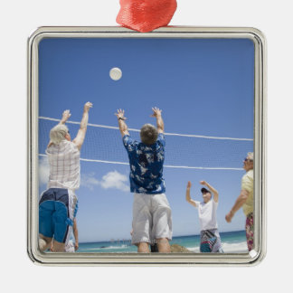 Mature men leaping for volley ball on beach, metal ornament
