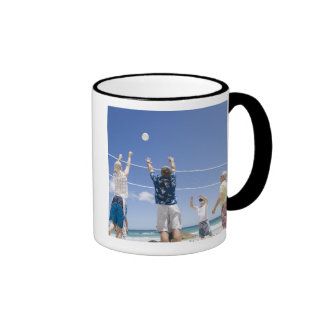 Mature men leaping for volley ball on beach mugs