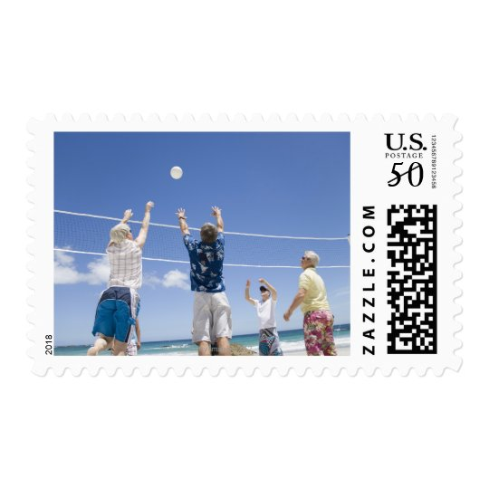 Mature men leaping for volley ball on beach, postage