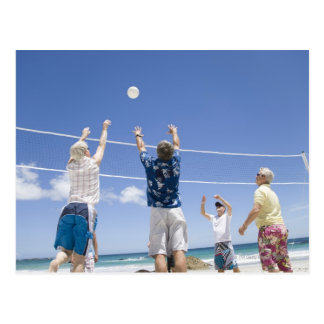 Mature men leaping for volley ball on beach, postcard
