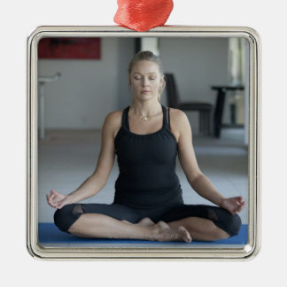 Mature woman practicing yoga square metal christmas ornament