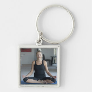 Mature woman practicing yoga Silver-Colored square keychain