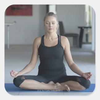 Mature woman practicing yoga square sticker