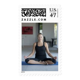 Mature woman practicing yoga stamp