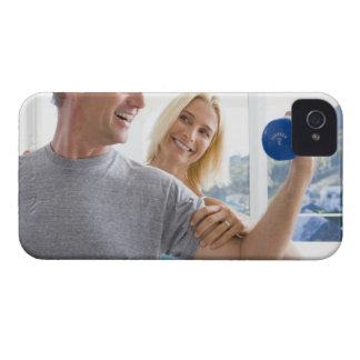 Mature woman smiling at mature man lifting iPhone 4 cover
