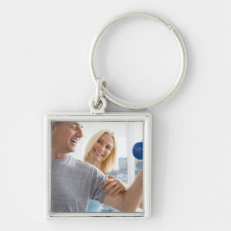 Mature woman smiling at mature man lifting Silver-Colored square keychain