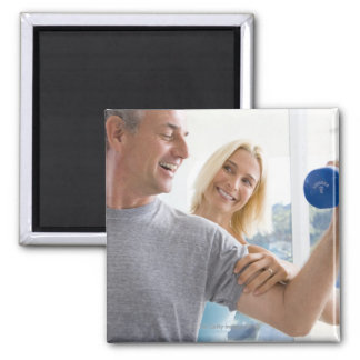 Mature woman smiling at mature man lifting magnet