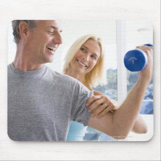 Mature woman smiling at mature man lifting mouse pad