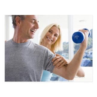 Mature woman smiling at mature man lifting postcard