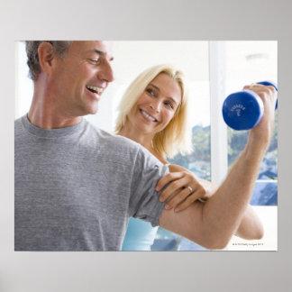 Mature woman smiling at mature man lifting poster