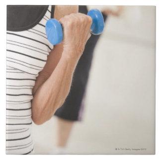 Mayores que ejercitan con pesas de gimnasia en una azulejo cuadrado grande