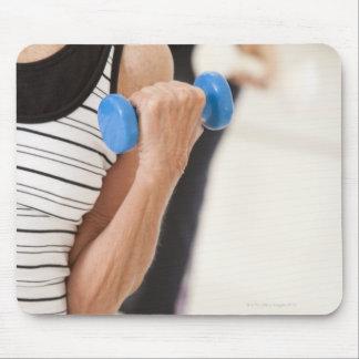 Mayores que ejercitan con pesas de gimnasia en una alfombrilla de ratón