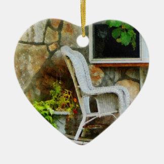 Mecedora de mimbre en el pórtico adorno navideño de cerámica en forma de corazón
