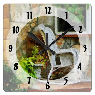 Mecedora de mimbre en el pórtico reloj cuadrado