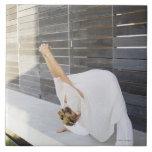 Mediados de mujer adulta que estira sus brazos azulejos cerámicos
