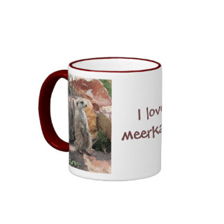 Meerkat que se coloca en las piernas traseras taza de café