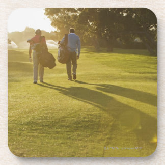 Men carrying golf bags on golf course beverage coaster