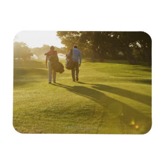 Men carrying golf bags on golf course magnet