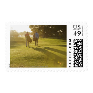 Men carrying golf bags on golf course postage