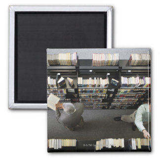 Men in library looking for books 2 inch square magnet