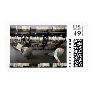 Men in library looking for books postage