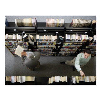 Men in library looking for books postcard