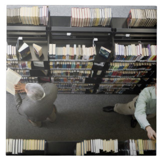 Men in library looking for books tiles