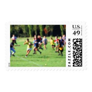 Men playing in park, defocused postage