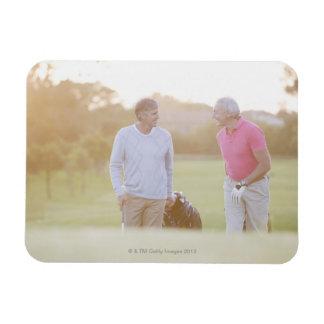 Men pulling golf carts magnet