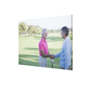 Men shaking hands on golf course canvas print