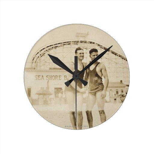 Men Standing on Beach Round Wall Clock
