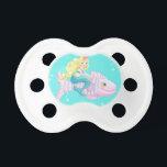 "Mermaid pacifier<br><div class=""desc"">Blonde mermaid pacifier on pink fish</div>"