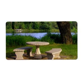 Mesa de picnic debajo de un árbol de sombra cerca  etiqueta de envío