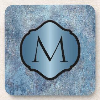 Metal azul sucio fotorrealista con monograma posavaso