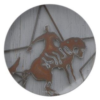 Metal sculpture of cowboy on bucking bronco plates
