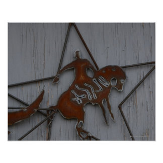 Metal sculpture of cowboy on bucking bronco poster