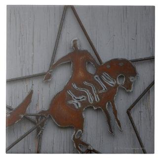 Metal sculpture of cowboy on bucking bronco tiles