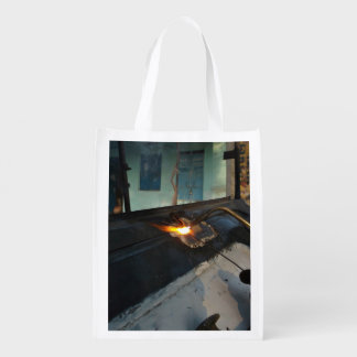 Metal Themed, A Man Carefully Welds A Large, Metal Reusable Grocery Bag