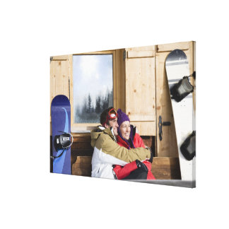 Mid adult couple embracing outside log cabin canvas prints