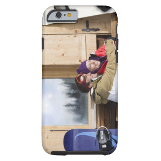 Mid adult couple embracing outside log cabin tough iPhone 6 case
