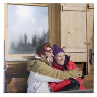 Mid adult couple embracing outside log cabin ceramic tile