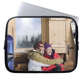 Mid adult couple embracing outside log cabin computer sleeve
