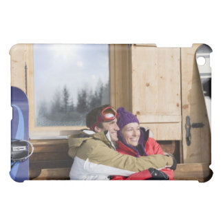 Mid adult couple embracing outside log cabin iPad mini case