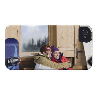 Mid adult couple embracing outside log cabin iPhone 4 case